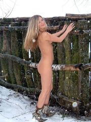 Nude girl posing in the snow in the..