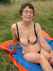 Nude Mature women with glasses near the..